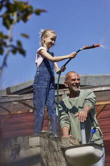 Grandfather and granddaughter with garden hose in allotment garden - MCF00870