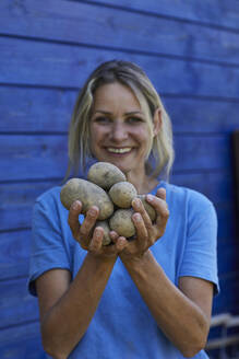 Portrait of happy woman holding potatoes at garden shed - MCF00903