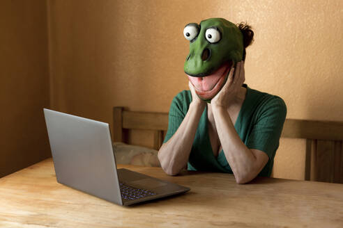 Playful mature woman wearing frog mask with laptop on table sitting at home during curfew - FLLF00489