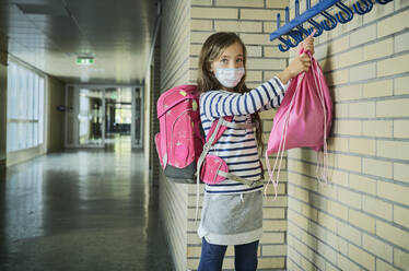 Girl wearing mask in school hanging up pouch - DIKF00501