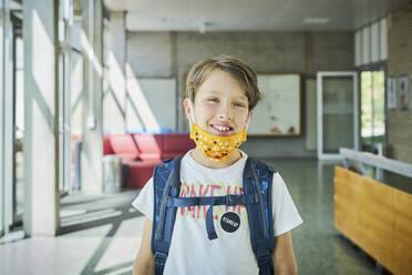 Portrait of smiling boy wearing mask in school - DIKF00504