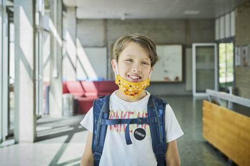 Portrait of smiling boy wearing mask in school - DIKF00504