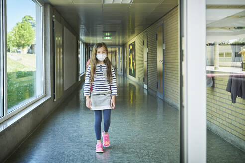 Girl wearing mask walking on school corridor - DIKF00507