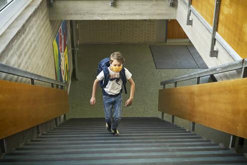 Boy wearing mask in school walking up stairs - DIKF00510