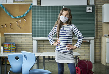 Portrait of confident girl wearing mask in classroom - DIKF00513