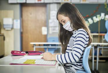 Girl wearing mask in classroom writing in workbook - DIKF00516