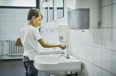 Boy wearing mask on school toilet washing his hands - DIKF00519