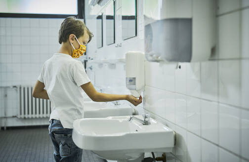 Boy wearing mask on school toilet washing his hands - DIKF00519