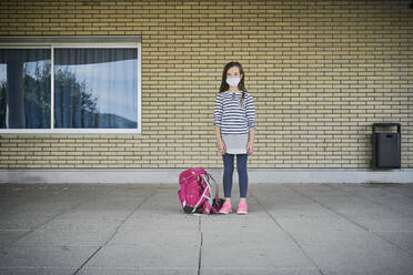 Girl with schoolbag wearing mask standing in front of building - DIKF00522