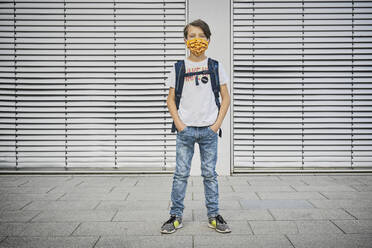Boy with schoolbag wearing mask standing in front of building - DIKF00525