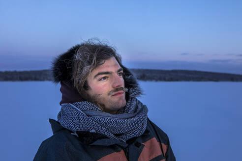 Portrait of man in winter landscape with frozen moustache, Ounasjaervi, Enontekioe, Finland - WVF01548