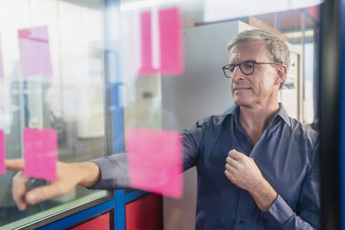 Mature businessman pointing at adhesive note on glass while planning strategy in office - DIGF11281