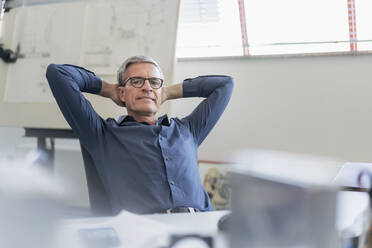 Portrait of confident male entrepreneur relaxing while sitting with hands behind head at office desk - DIGF11302