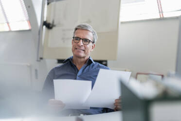 Smiling mature male entrepreneur sitting with document while contemplating at desk in office - DIGF11305