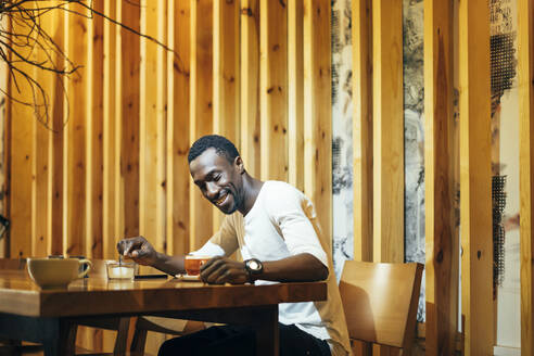 Smiling young man looking at coffee on table while sitting against wall in cafe - OCMF01257