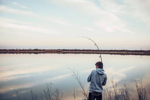 Rear view of teenage boy wearing hooded shirt fishing with rod in lake against cloudy sky - ACPF00715