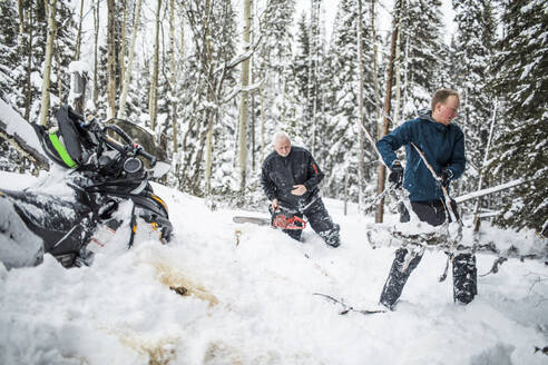 Father and son clearing trails while snowmobiling. - CAVF82037