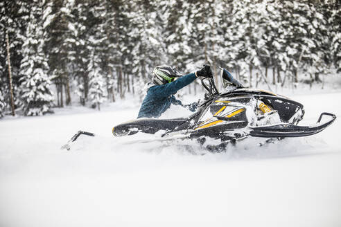 Side view of man turning snowmobile in deep powder. - CAVF82046