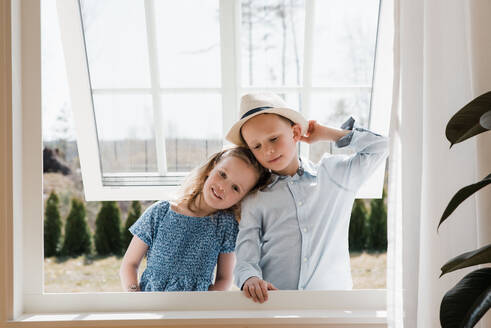 Brother and sister hugging whilst looking through a window at home - CAVF82124