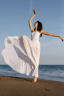 Ballerina in white dress dancing at the sea - TCEF00688