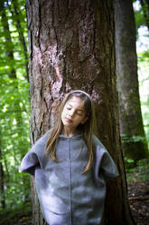 Young girl with eyes closed standing against tree trunk in forest - LVF08904
