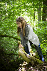 Cute girl climbing on tree in forest - LVF08907