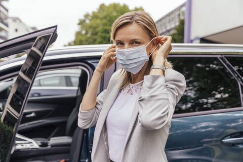 Portrait of woman standing in front of her car putting on protective mask - MFF05603