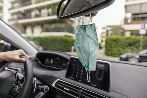 Protective mask hanging from rear-view mirror in car - MFF05612
