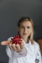 Hand of female scientist holding 3D model of SARS-CoV-2 virus, close-up - MFF05630
