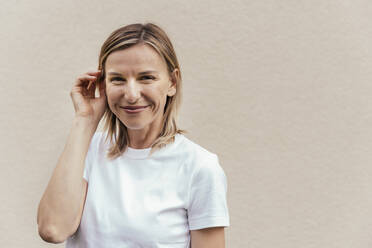 Portrait of smiling blond woman wearing white t-shirt in front of light wall - MFF05633