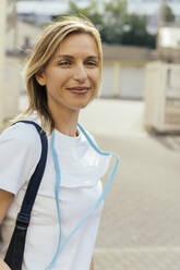 Portrait of smiling blond woman with protective mask outdoors - MFF05651