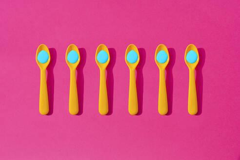 Studio shot of row of yellow plastic teaspoons with blue liquid - GEMF03756