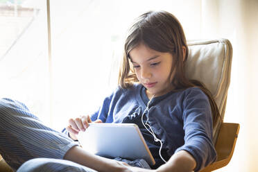 Girl watching video online while sitting on armchair against window at home - LVF08910