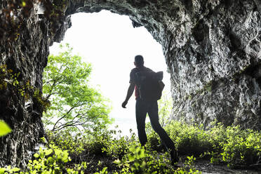 Mature man exploring while walking amidst plants in cave - MCVF00395