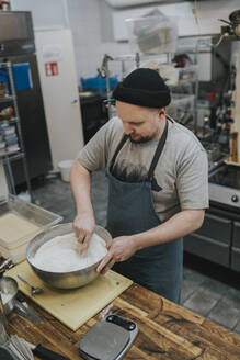 Male chef mixing flour in bowl at commercial kitchen counter - PSIF00391