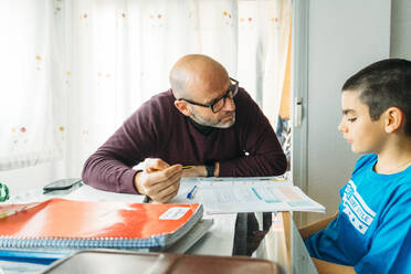 Father explaining son sitting at desk during homeschooling - JCMF00763