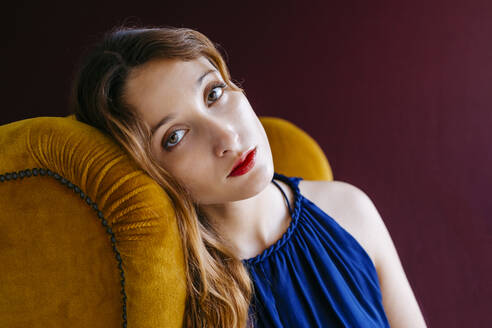 Close-up portrait of confident young woman sitting on golden chair against magenta background - TCEF00712