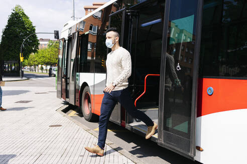 Young man wearing protective mask getting off public bus, Spain - DGOF01008