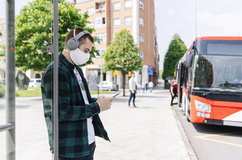 Young man with headphones wearing protective mask using smartphone while waiting at bus stop, Spain - DGOF01014