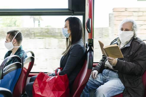 Passengers wearing protective masks in public bus, Spain - DGOF01041
