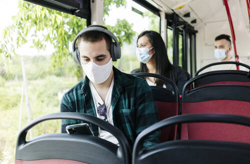 Portrait of young man with headphones wearing protective mask in public bus using cell phone, Spain - DGOF01047