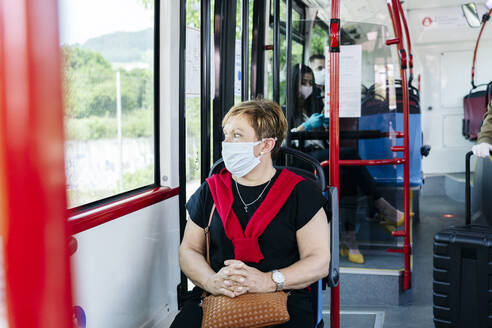 Portrait of mature woman wearing protective mask in public bus looking out of window, Spain - DGOF01062