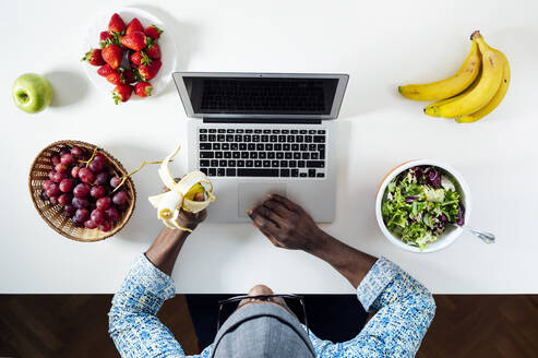 Man working while eating at desk in home office - JCMF00775