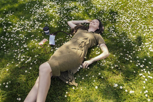 Happy woman enjoying her free time while lying on grass with daisies next to face mask - MFF05706