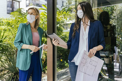 Two real estate agents wearing face masks while inspection outdoor area of house - MFF05712