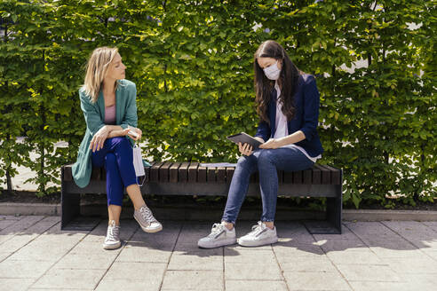 Two businesswomen sitting on bench outside and keeping their distance while wearing face mask - MFF05724