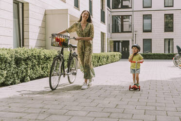 Smiling mother with bicycle and son with scooter in the city - MFF05727