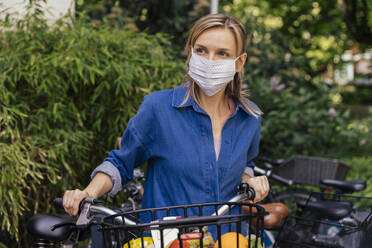 Woman wearing face mask with bicycle and shopped groceries in urban area - MFF05736