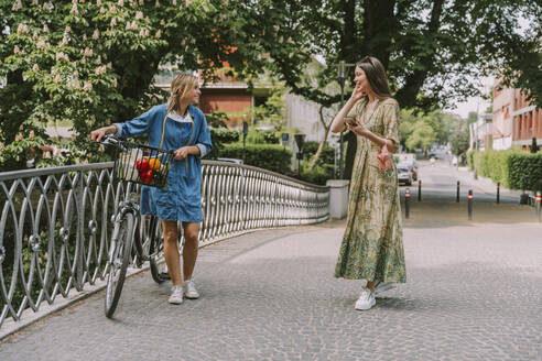 Two women with bicycle and face mask walking on a bridge - MFF05751