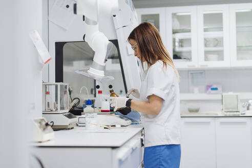 Female scientist with long brown hair working at laboratory - OCAF00499